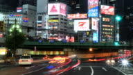 MS T/L Shot of traffic and trains passing through colorful neon's of Shinjuku at night / Tokyo, Japan