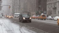 Shot of traffic moving along Central Park West Avenue, outside of Central Park , New York City on a snowy winter day.