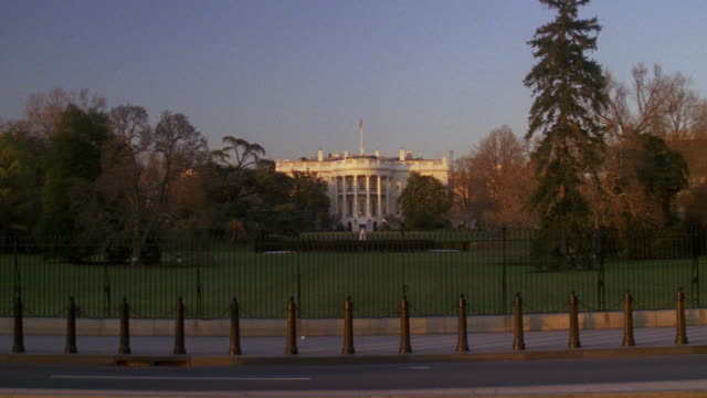 MS Shot of traffic moving on road in front of White House / Washington D.C., United States