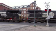 MS Shot of train going by railroad crossing in center of city / Greensboro, North Carolina, United States
