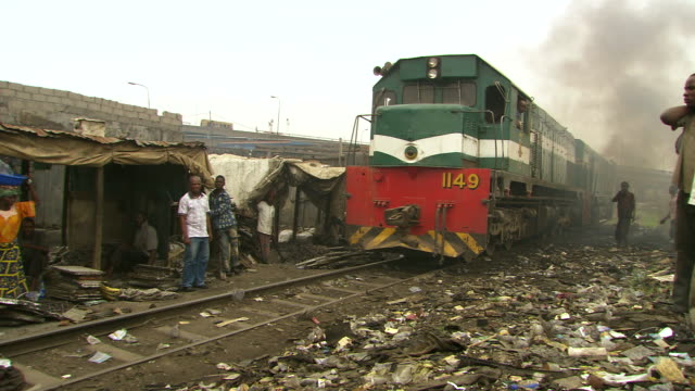 Shot of train track running through shanty town and burning plastic with people standing / Lagos Nigeria