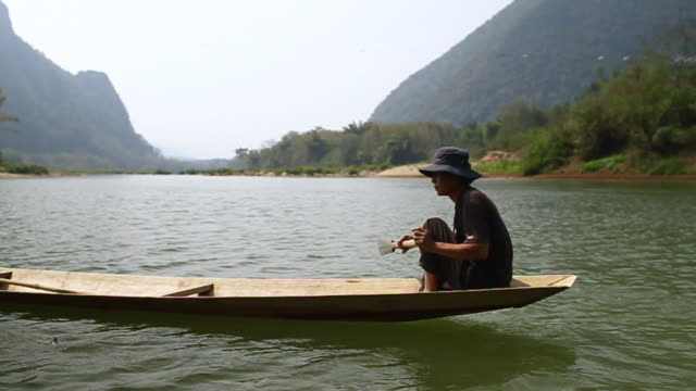 MS SLO MO Shot of Travelling following man rowing wooden canoe in river / Ou river, Luang Prabang, Laos