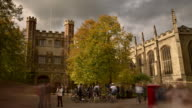 MS T/L Shot of Trinity college cambridge sunny autumn day passing fluffy clouds locals tourist and students passing with dramatic changing light / London, Greater London, United Kingdom