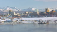 MS AERIAL ZO Shot of tug boats at port and downtown / Anchorage, Alaska, United States