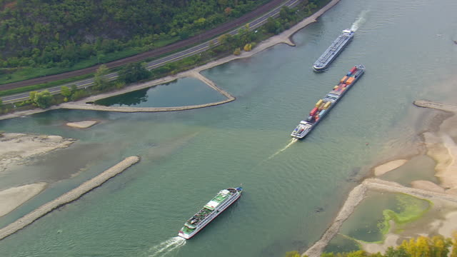 MS AERIAL Shot of tug boats moving in river with road and rail track along hill at upper middle Rhine valley / Germany