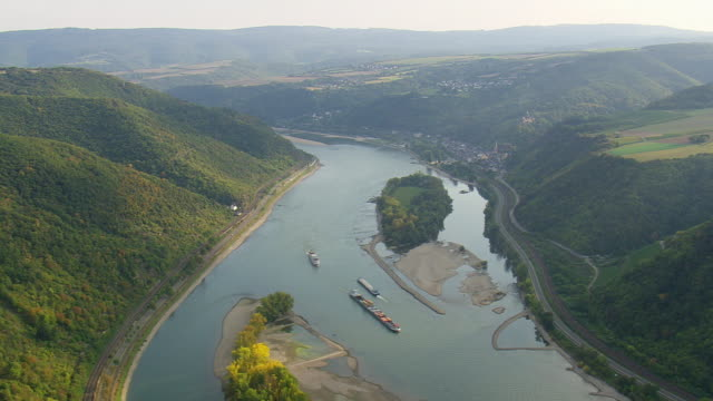 MS AERIAL Shot of tug boats moving in river with road and rail track along hill with farmland at upper middle Rhine valley / Germany
