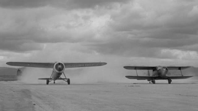 MS Shot of two airplanes sitting on dirt runway with propellers spinning planes begin moving forward