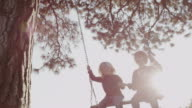 MS LA SLO MO Shot of two boys swing on large wooden country swing out on farm with sun flares / Hood River, Oregon, United States