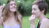 'MS Shot of Two friends wearing floral wreath and eating strawberries / Berlin, Germany'