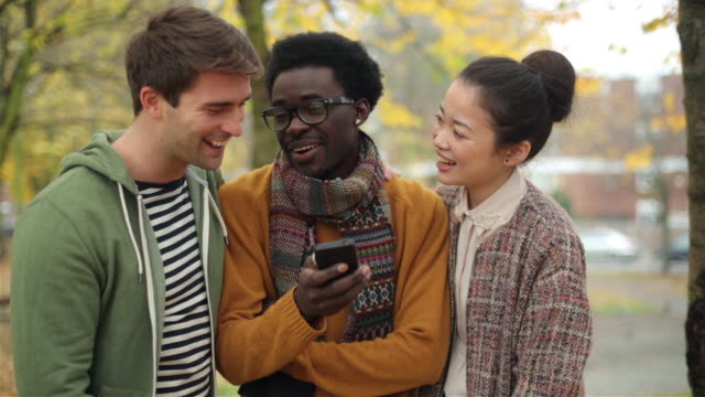 MS Shot of two guys and pretty Asian woman laughing and smiling by looking in mobile phone / London, United Kingdom