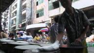 MS Shot of Two men baking bread (pancakes?) on hotplates on street / Yangon, Yangon Division, Myanmar