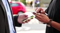 CU Shot of two men exchanging information by bumping smart phones / Santa Cruz, California, United States