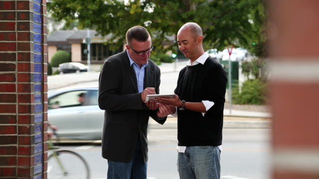 MS Shot of two men standing and signing tablet with electronic signature / Santa Cruz, California, United States