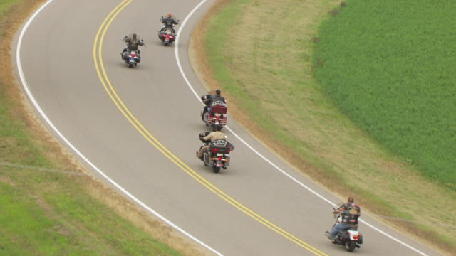 WS AERIAL TS ZO Shot of two motorcycle riders in side profile riding and riders driving curve along country road in Sauk County / Wisconsin, United States
