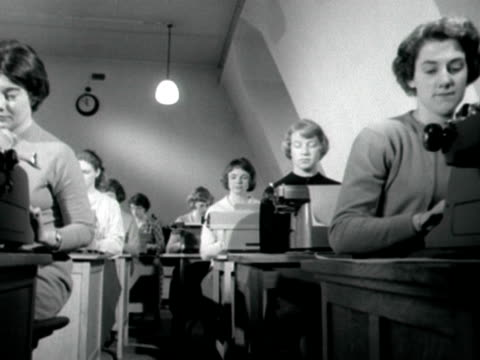 Shot of two rows of young women seated at desks and typing at the BBC secretarial school 1959