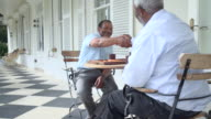 MS ZI Shot of Two senior African men playing backgammon on patio / Cape Town, Western Cape, South Africa