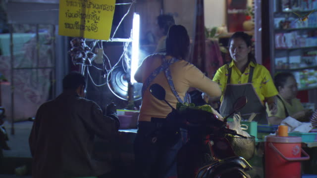 MS Shot of Two street vendors prepare food as man eating at their food stall on Mae Sai main street at night / Mae Sai, Chiang Rai, Thailand