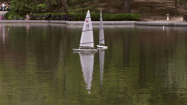 Shot of two toy sailboats blowing in the wind in Conservatory Water in Central Park, NYC on a sunny day