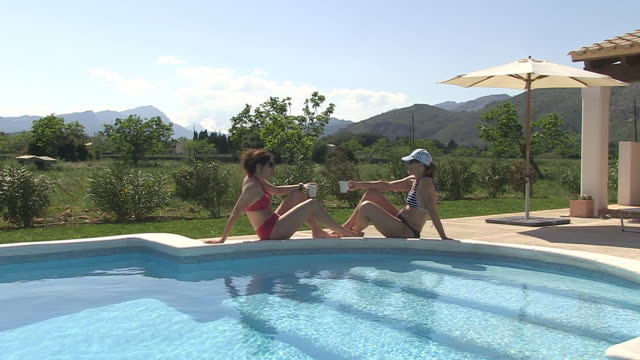 WS Shot of two woman drinking coffee at pool in holiday / Puerto Pollenca, Mallorca, Balearic Islands, Spain