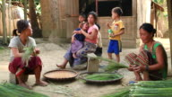 MS SLO MO Shot of Two women sitting and tying long grass together and another woman holding baby with boy standing next to her looking occasionally at towards / Muang Ngoi, Luang Prabang, Laos