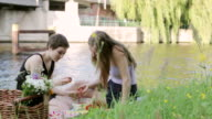 'MS Shot of Two young women sitting by Spree river, Germany, picnicking and eating strawberries / Berlin, Germany'