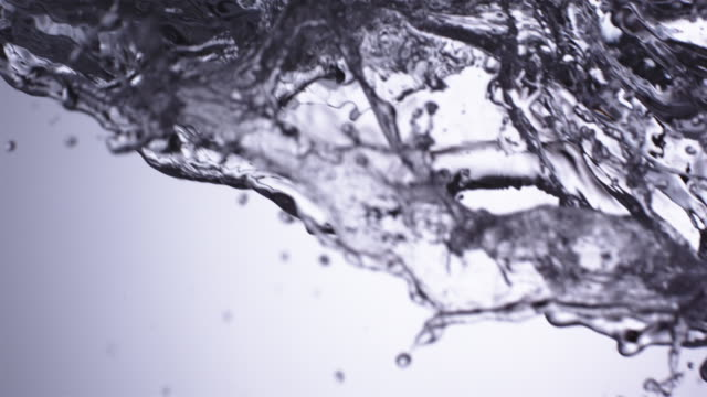CU SLO MO Shot of uncontrolled wave of water with ice cubes falling through frame against grey blue back drop / United Kingdom