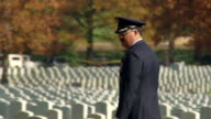 WS TS Shot of uniform officer walking right to left among white tombstones at Arlington National Cemetery / Washington, District of Columbia, United States