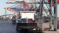 MS Shot of unloading containers in container ship on container terminal with trolley in harbour / Hamburg, Germany
