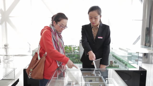MS PAN Shot of Visitor and saleswoman talking about apartment models in real estate sales center / Xi'an, shaanxi, China