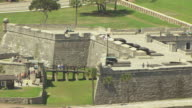 CU AERIAL ZO Shot of visitors walking by cannons at fort Castillo de San Marcos and Matanzas River and landscape surrounding fort / St Augustine, Florida United States