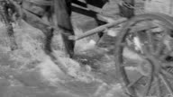 CU LA Shot of wagon train traveling through riverbed and horses legs with wagon wheels through shallow water