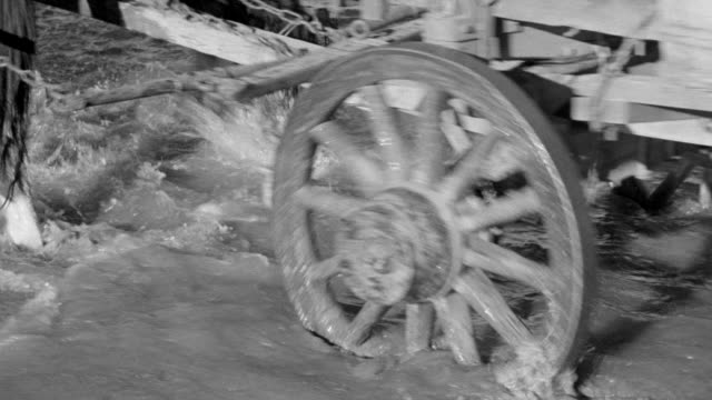 CU TU Shot of wagon train traveling through riverbed and horses legs with wagon wheels through shallow water
