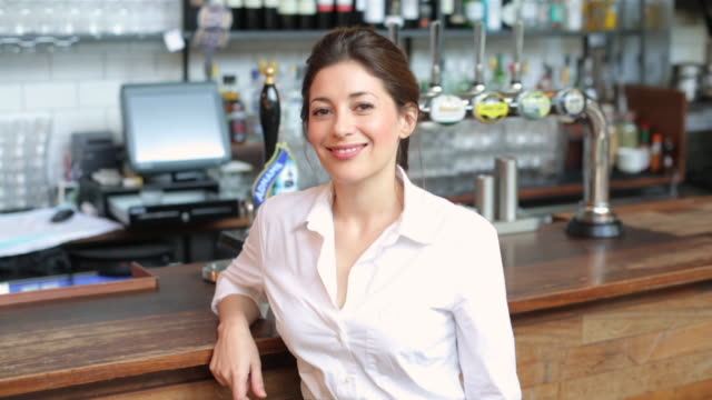 MS Shot of waitress woman standing near table in bar / London, United Kingdom