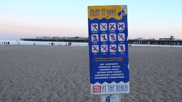 MS Shot of Warnings about everything on beach forbidden rules safety / Santa Cruz, California, United States