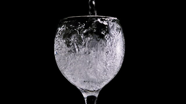 CU SLO MO Shot of Water being poured into glass / Calvados, Normandy, france