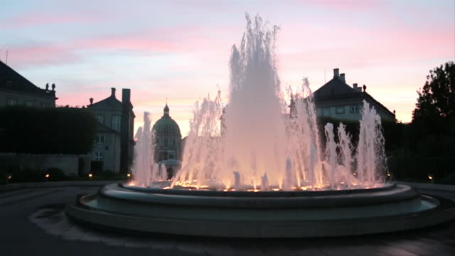 MS SLO MO Shot of water spraying out of water fountain in middle of street at sunset with buildings all around / Copenhagen, Denmark