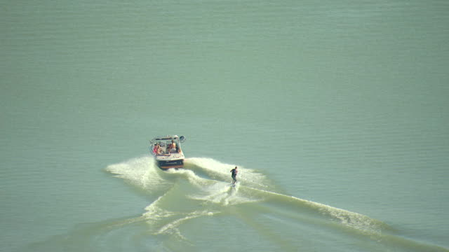 MS AERIAL Shot of waterboarder being pulled by speedboat skis on boulder reservoir water in boulder county / Colorado, United States