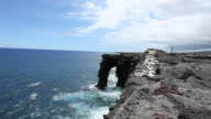 WS Shot of waves crashing again Holei Sea Arch in Volcanoes National Park on sunny day / Volcano, Hawaii, Big Island, United States