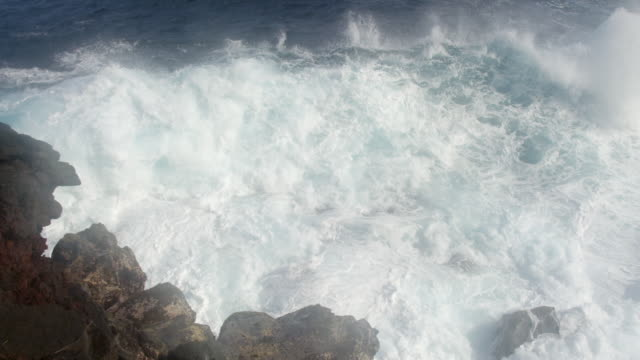 MS PAN SLO MO Shot of waves crashing into rocks with big splash / Waipio, Hawaii, United States