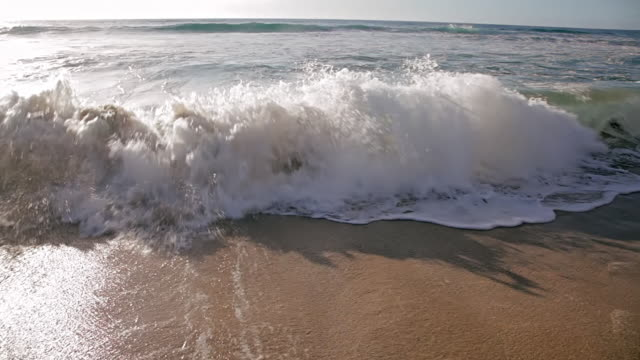 CU Shot of waves crushing to sandy beach / Polihe Beach, Kauai Hawaii, United States
