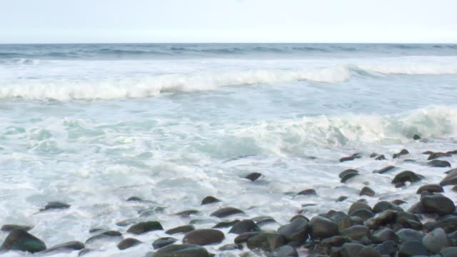 MS PAN Shot of waves hit sandy beach with black rocks / Kona, Hawaii, United States