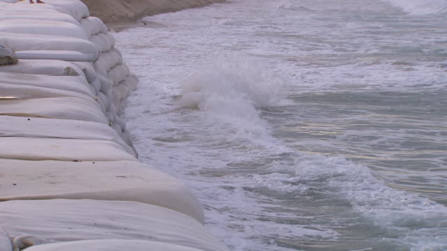 MS TS Shot of Waves splashing on sandbag wall / Kingscliff, New South Wales, Australia
