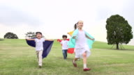 MS SLO MO Shot of Wearing cloth sheet childrens running down / Seoul, South Koreameadow hill