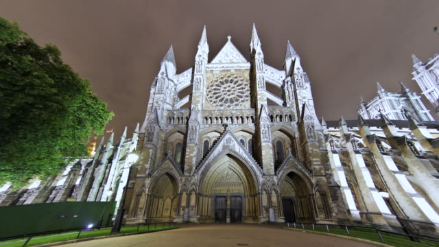 MS T/L Shot of Westminster Abbey at evening with some tourists walking around / London, United Kingdom