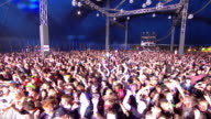 WS POV PAN Shot of White and blue flashing lights in and out of crowd with jumping up and down going wild hands up in air / Isle of Wight, London, United Kingdom