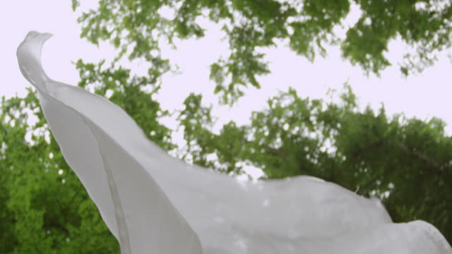 'CU TD SLO MO Shot of white sheet flowing through air in forest / Berlin, Germany'