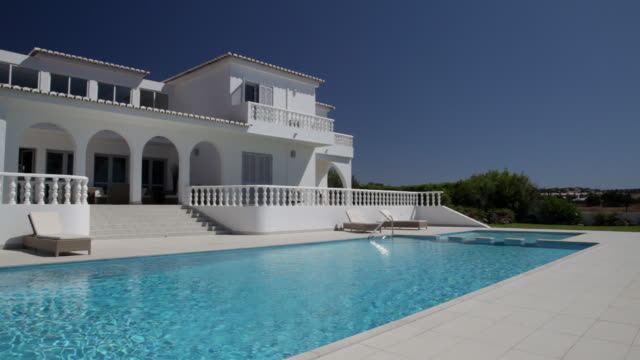¾ shot of white villa with colonnades and pool.