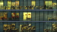 MS T/L Shot of Windows of office block of people at work / London, United Kingdom