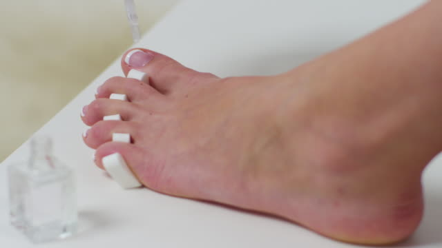 CU Shot of woman applying toe nail polish / Santa Cruz, California, United States