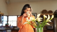 MS Shot of woman arranging flowers in vase and drinking coffee at home / Lamy, New Mexico, United States